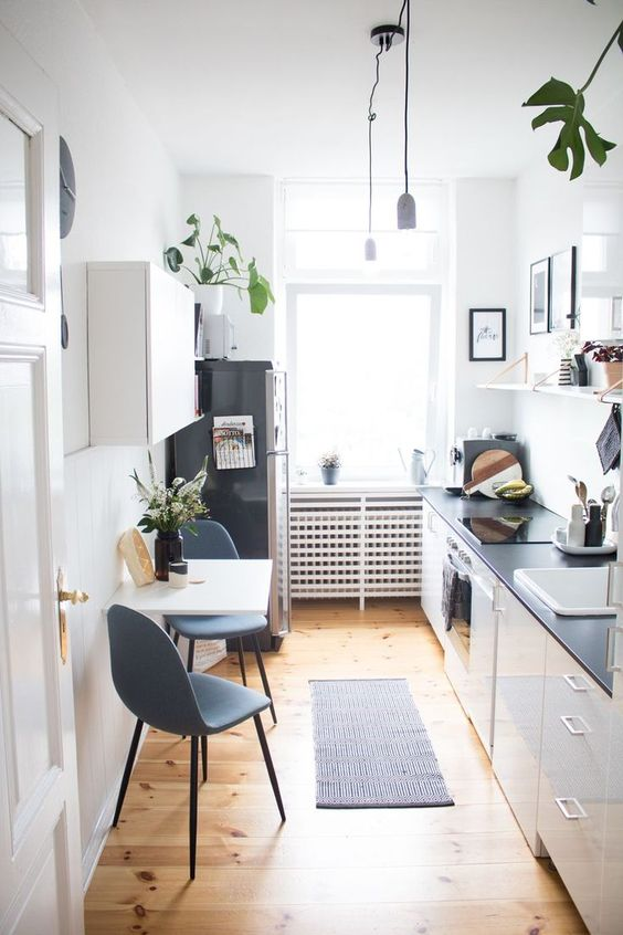 a chic white kitchen with black countertops, open shelves, a folding table and grey chairs plus plants