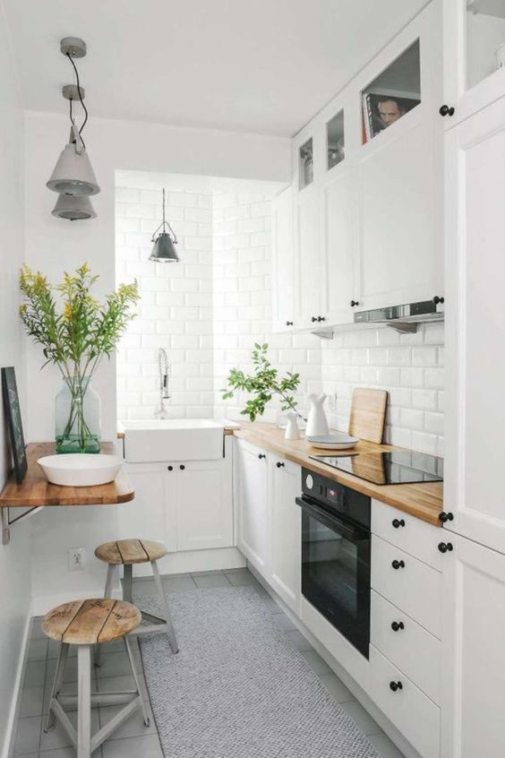 a chic white kitchen with butcherblock countertops, a folding table and stools and vintage pendant lamps