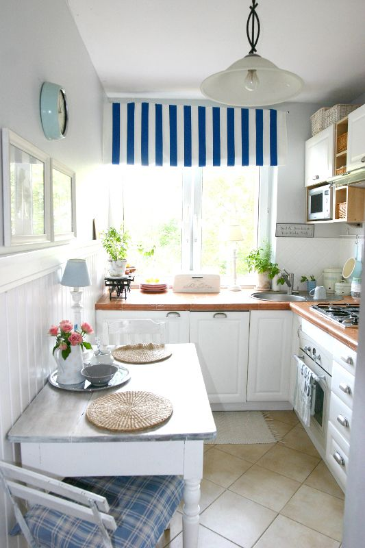 a cozy coastal kitchen with white cabinetry, bold countertops, striped and plaid textiles and a pendant lamps