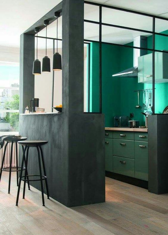 a dark green kitchen cube with emerald walls and cabinets inside, butcherblock countertops and pendant lamps