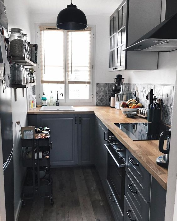 a graphite grey kitchen with butcherblock countertops, a black cart and a black pendant lamp and grey printed tiles
