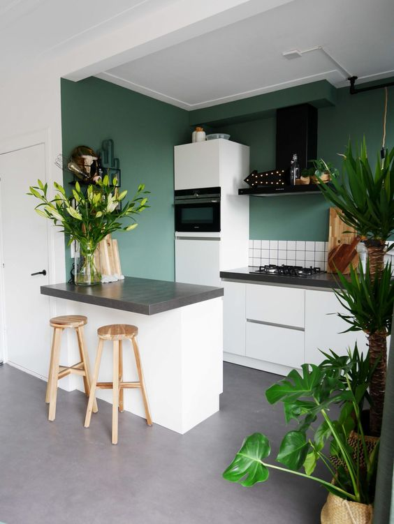 a green kitchen with white tiles, grey stone countertops, a black hood and potted plants and blooms