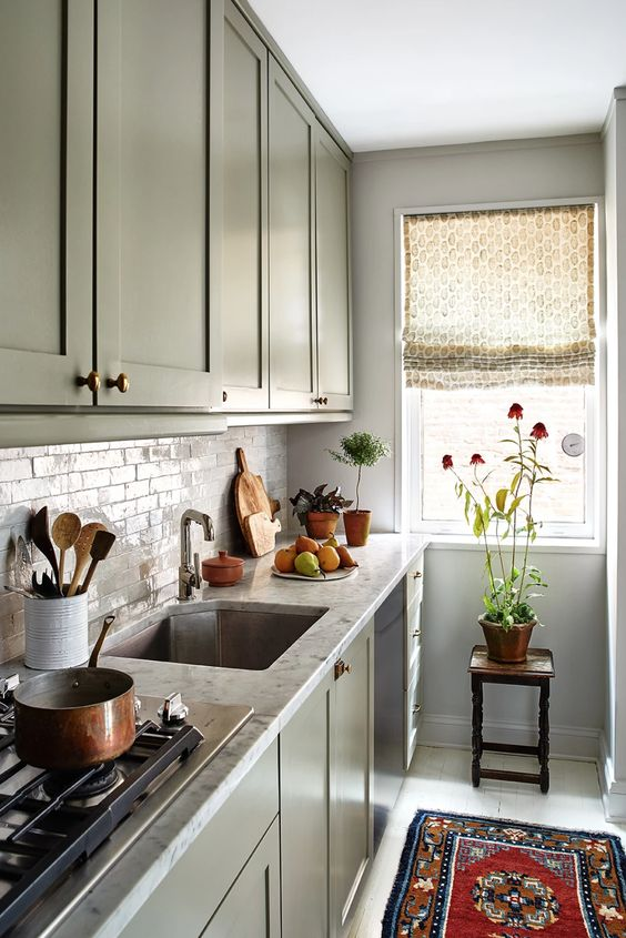 a green one wall kitchen with stone countertops and a tile backsplash and some printed textiles is chic