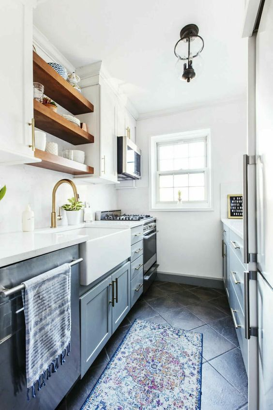 a grey and white kitchen with open shelves, gold touches and printed rugs is a cool space