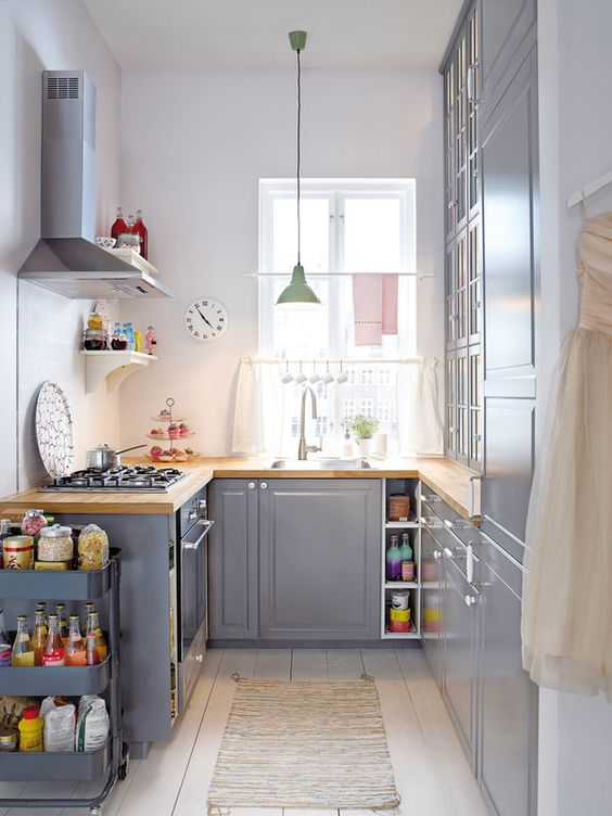 a grey kitchen with butcherblock countertops, a pastel pendant lamp and a grey cart  for additional storage