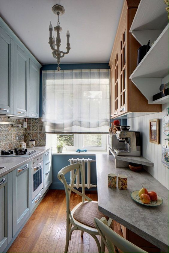 a light blue kitchen with blue walls, stained and blue cabinets, concrete countertops and a vintage pendant lamp