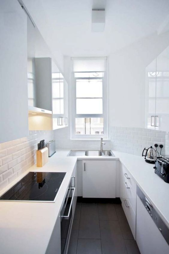 a minimalist all-white kitchen with white skinny tiles, a window, built-in appliances in black is pure chic