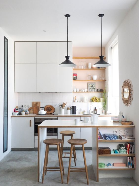 a modern white kitchen with open built-in shelves, a kitchen island with shelves and pendant lamps