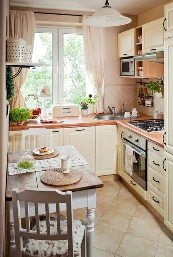 a neutral French country style kitchen with a tile backsplash, neutral textiles, a small table and floral chairs