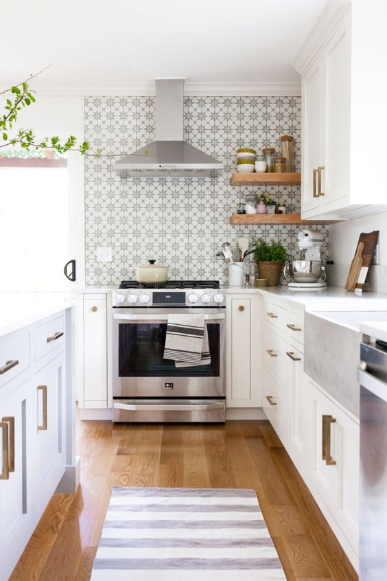a pretty neutral kitchen with a printed tile backsplash, brass handles, potted greenery and woven planters