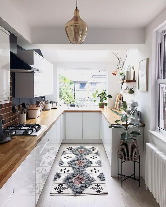 a pretty small kitchen with white cabinets, butcherblock coutnertops, potted plants and a printed rug
