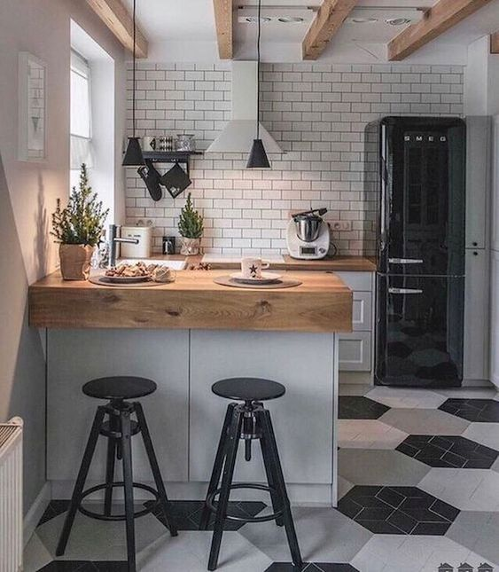 a small Scandinavian kitchen in black, white and grey, with butcherblock countertops and a white tile backsplash and pendant lamps