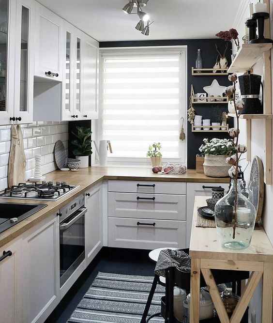 a small Scandinavian kitchen with a white tile backsplash, butcherblock countertops, open shelves and black walls
