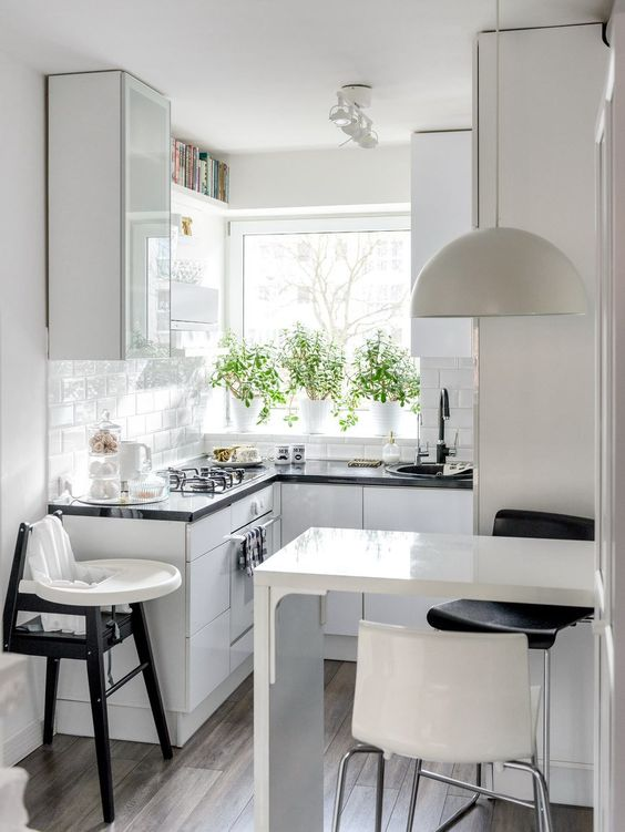 a small Scandinavian kitchen with white glossy cabinets, black countertops, a bar countertop, a pendant lamp and stools