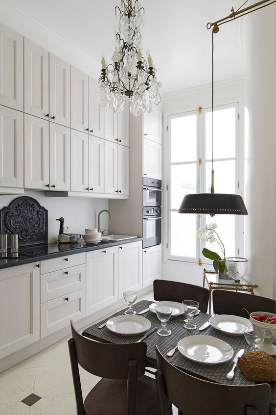 a small and chic French style kitchen with black coutnertops, a crystal chandeliers, a small dining zone with an additional lamp