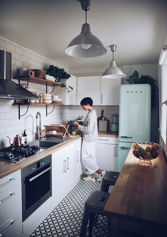 a small and cozy Scandinavian kitchen with white cabinets, butcherblock countertops, a mint fridge and a white tile backsplash