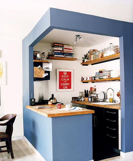 a small kitchen cube with blue walls, black cabinets, open shelves and butcherblock countertops is super cool