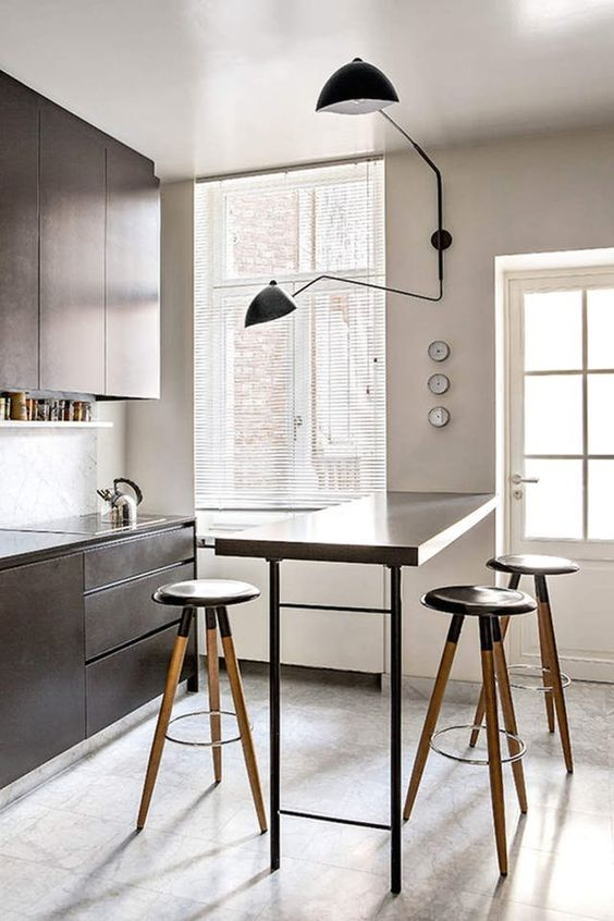 a small kitchen with sleek brown cabinetry, a tall bar countertop and tall stools plus a cool sconce