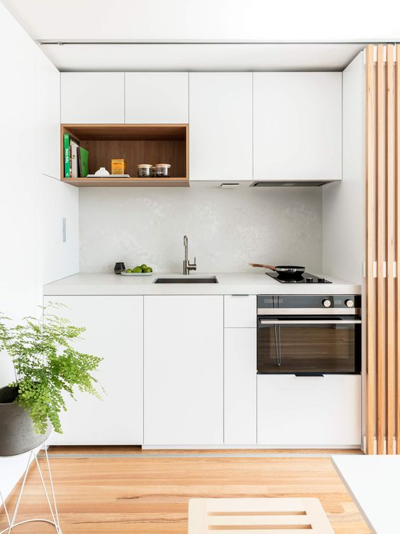 a small minimalist kitchen in white, with a white tile backsplash and a white stone countertop that can be hidden with a screen