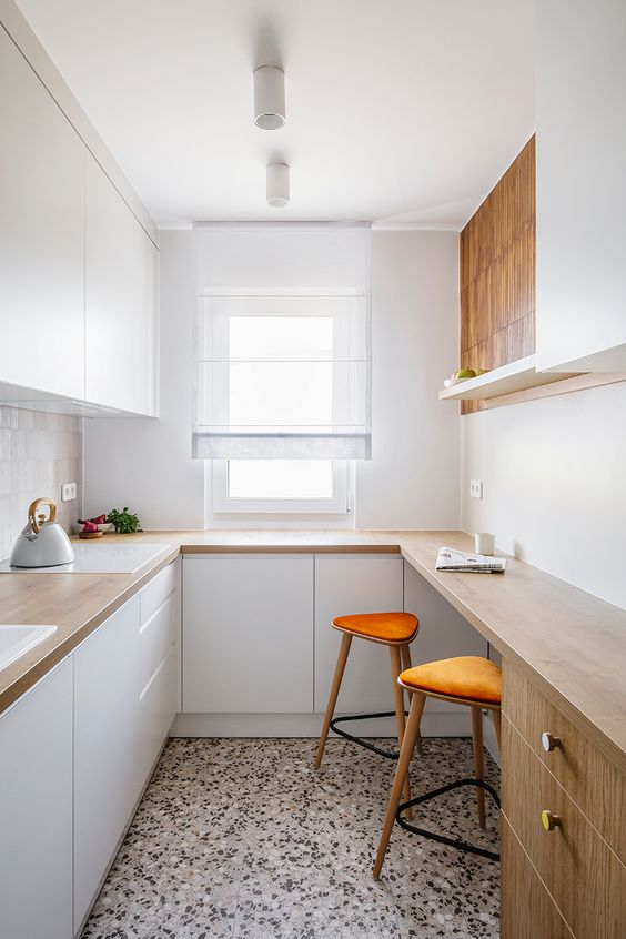 a small minimalist kitchen with sleek white cabinetry, butcherblock countertops and a bar counter for cooking and eating