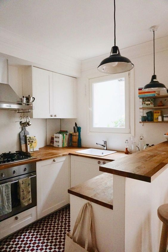a small modern white kitchen with butcherblock countertops a kitchen island with two tops, retro pendant lamps
