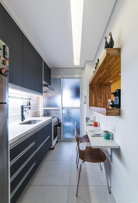 a small sleek black kitchen with a thick white stone countertop, a white tile backsplash, a built-in shelf with a coffee machine and a bar table