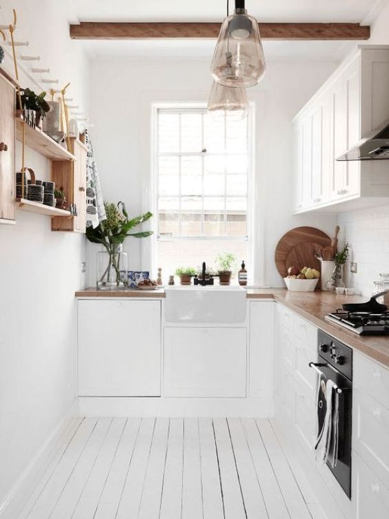 a small white Scandinavian kitchen with butcherblock countertops, a stained wooden shelf and wooden beams on the ceiling