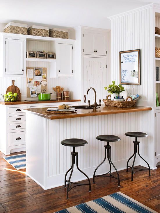 a small white farmhouse kitchen with stained wooden countertops, black stools, boxes and baskets is welcoming