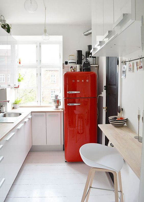 a small white kitchen in Scandinavian style, blonde wood countertops, a bold red fridge for a touch of color