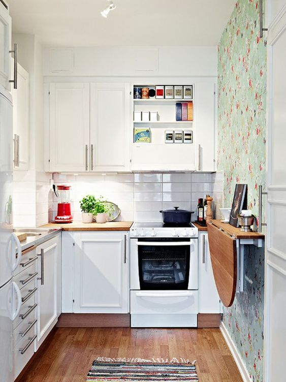 a small white kitchen with a white skinny tile backsplash, a floral wallpaper wall, a folding table and a printed rug