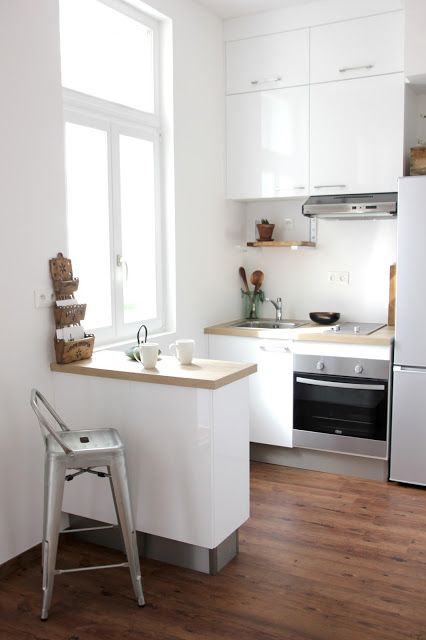 a small white kitchen with butcherblock countertops, a bar countertop that acts as a kitchen island