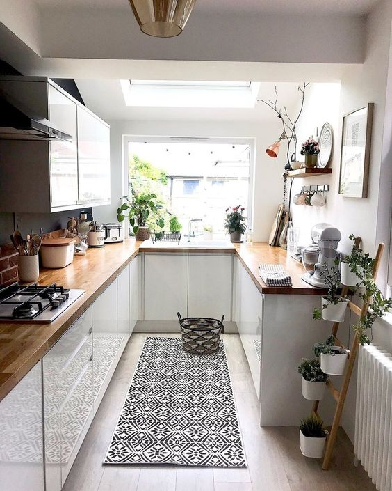 a small white kitchen with butcherblock countertops, potted greenery, a printed rug and pendant lamps