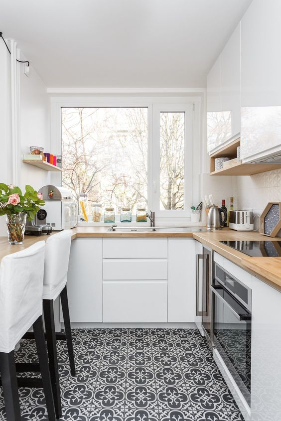 a small white kitchen with butcherblock countertops, white stools and a window with a view