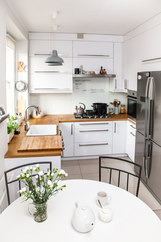 a small white kitchen with butcherblock coutnertops, stainless steel appliances and a round table and chairs