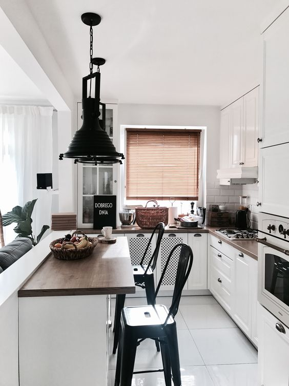 a small white kitchen with dark stained countertops, white tiles on the backsplash, dark pendant lamps and black stools
