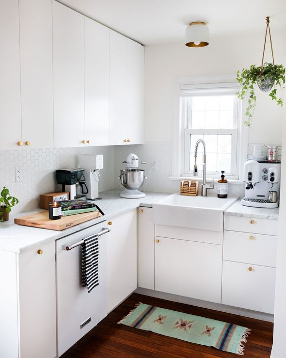 a small white kitchen with penny tiles, with white stone countertops, gold knobs and potted greenery