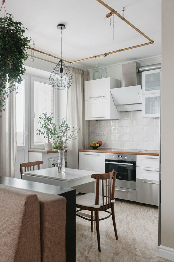 a small white kitchen with stained countertops, a white tile backsplash, a mini folding table and chairs