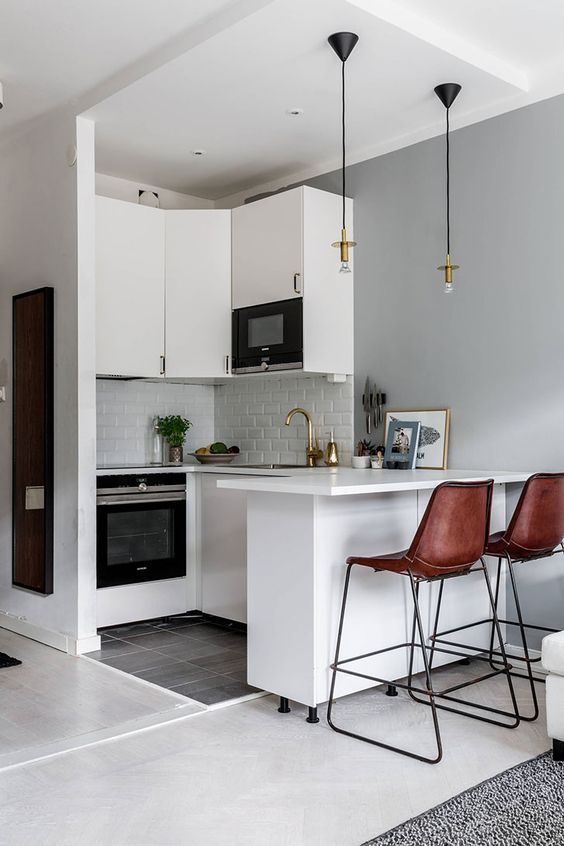 a small white kitchen with white tiles, pendant lamps, brown leather stools and gold touches is chic