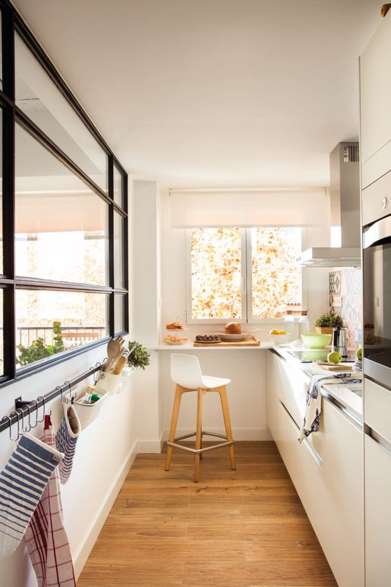 a small yet welcoming white minimalist kitchen with neutral countertops, a large window, a holder for towels and a windowsill bar