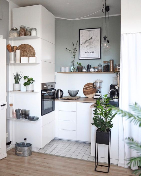a tiny Scandinavian kitchen with sleek white cabinets, some open shelves and built-in appliances plus pendant lamps