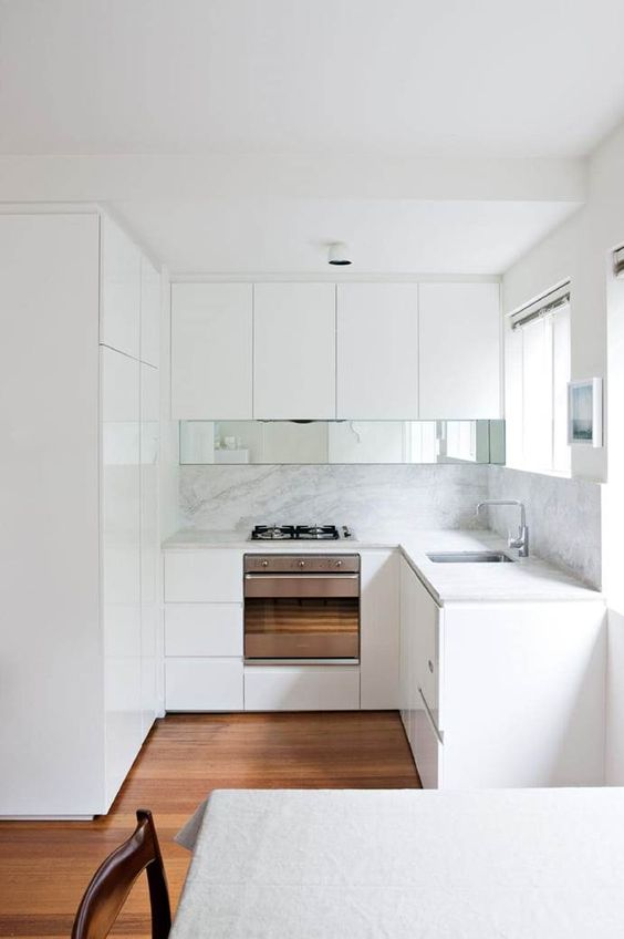 a tiny minimalist kitchen with a white backsplash and countertops, a mirror touch and an eating space