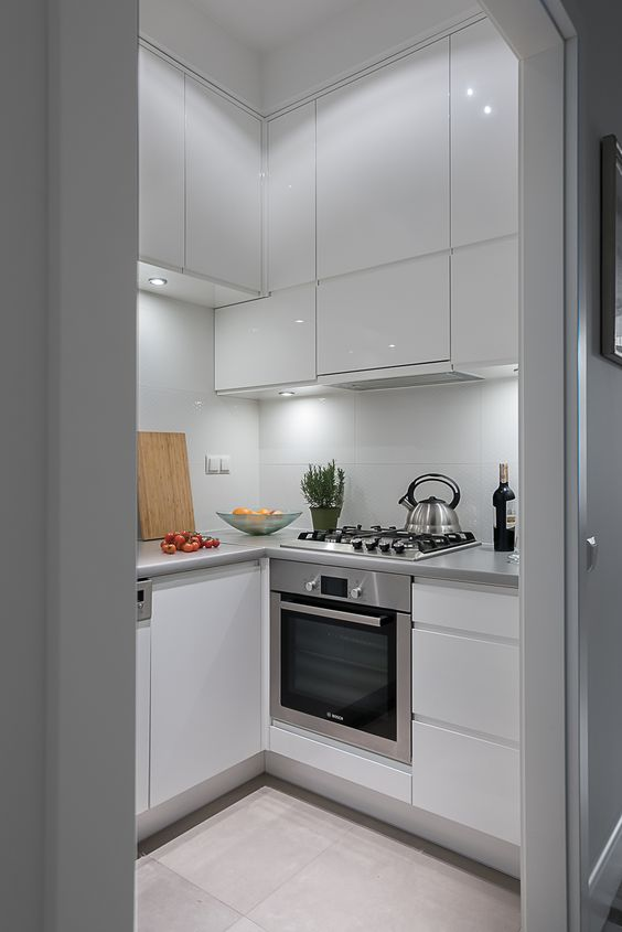 a tiny white sleek kitchen with built-in lights, metal countertops, built-in appliances is chic and cool