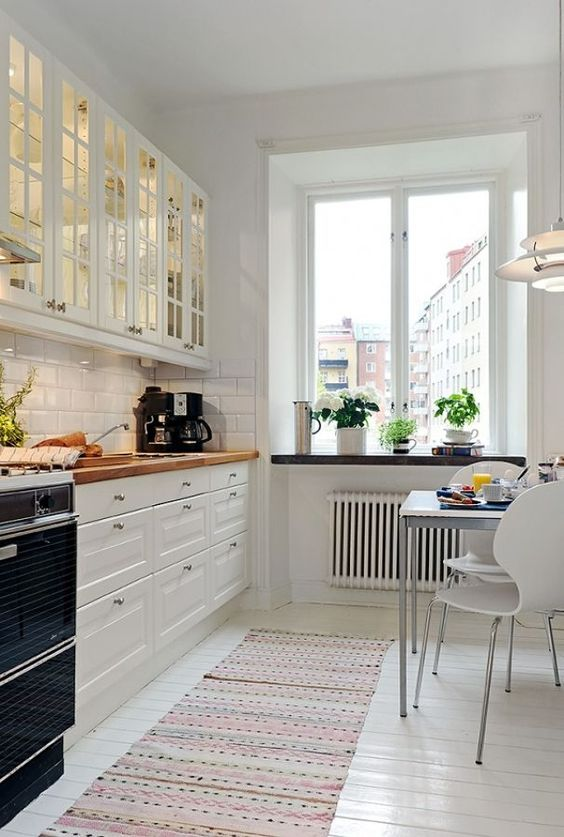 a welcoming white Scandinavian kitchen with glass cabinets, white tiles, butcherblock countertops and a small eating zone