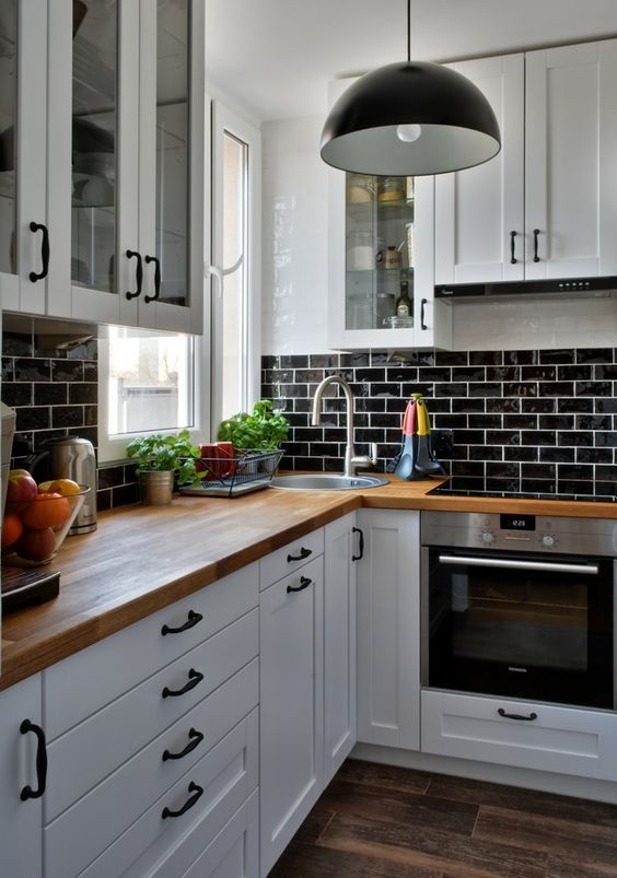 a white farmhouse kitchen with a black glazed tiles, butcherblock countertops, black pendant lamps