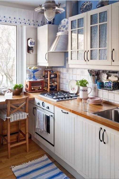 a white farmhouse kitchen with butcherblock countertops, tall stools and blue touches for coziness