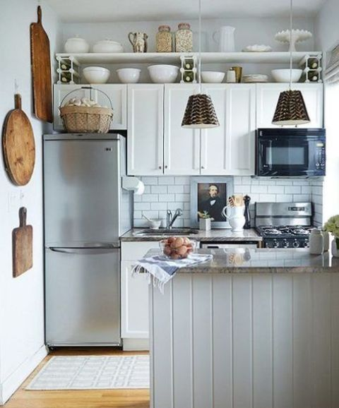 a white farmhouse kitchen with subway tiles, a kitchen island and pendant lamps and wooden touches