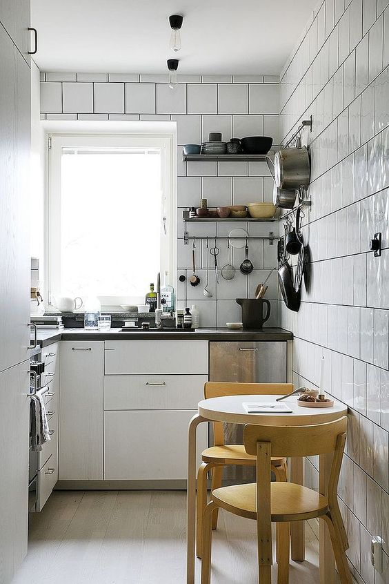 a white modern kitchen completely clad with tiles, black countertops, a round table and stools is comfy