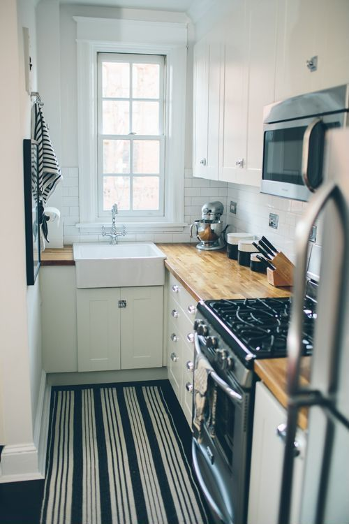a white modern kitchen with butcherblock countertops, a white tile backsplash, a striped rug and neutral handles