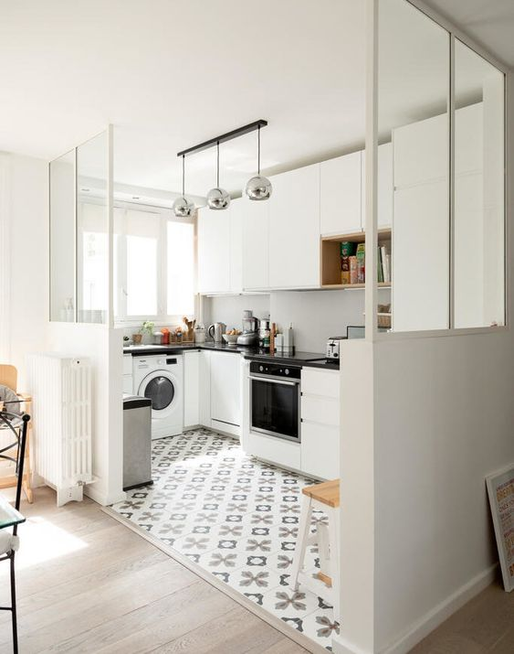 a white sleek kitchen with a white backsplash, black coutnertops and metallic lamps plus a printed tiled floor