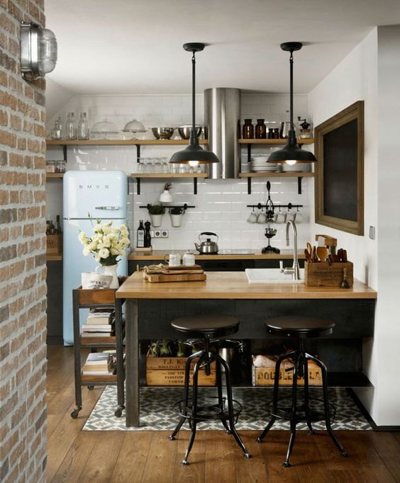 an industrial kitchen with blakc cabinetry, butcherblock countertops, a white tile backsplash and pendant lamps